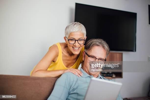 glückliche frau ihres mannes schultern gelehnt und mit blick auf seine digital-tablette - heterosexuelles paar stock-fotos und bilder