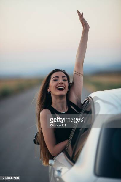Happy woman leaning out of car window