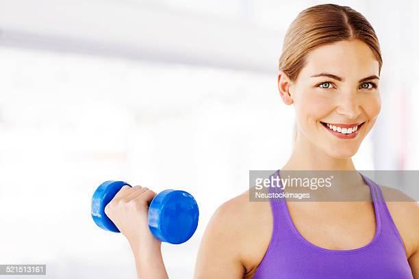 Glückliche Frau Gewichte im Fitness-Club