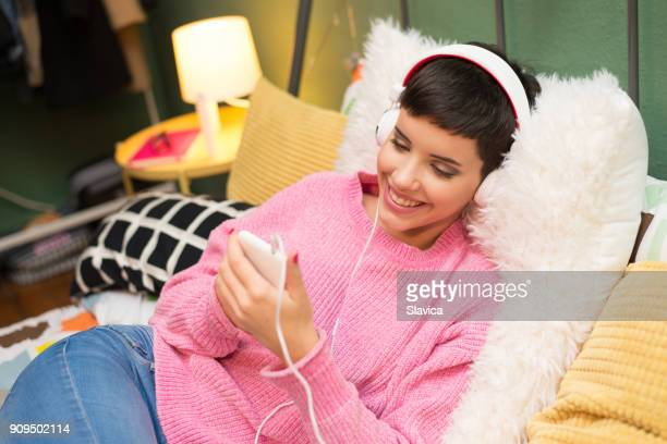 Happy woman listening music in bed