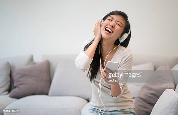 happy woman listening to music at home - chinese music stock pictures, royalty-free photos & images