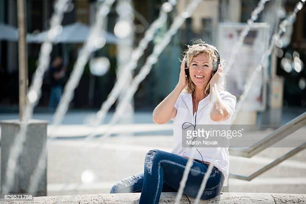 Happy woman listening to music in headphones