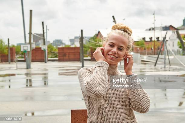 happy woman listening to music on windy day - aalborg stock pictures, royalty-free photos & images