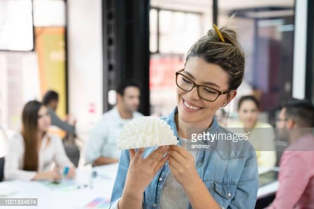 Happy woman looking at a 3D prototype at a design studio