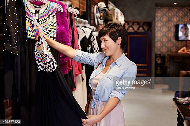Happy woman looking at dress in shop