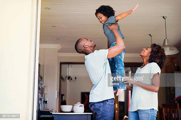 happy woman looking at man lifting son - black man holding baby stock photos and pictures