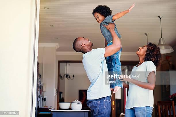 Happy woman looking at man lifting son