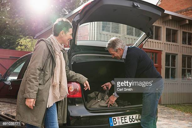 Happy woman looking at man putting bag in car trunk