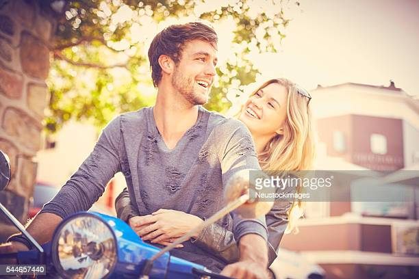 Happy woman looking at man riding motor trendy scooter