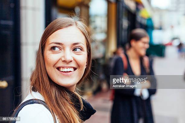 Happy woman looking away at city street