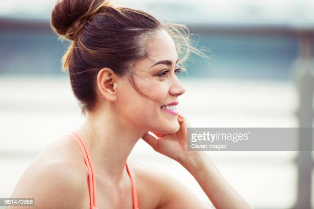 happy woman looking away while exercising - おだんごヘア ストックフォトと画像