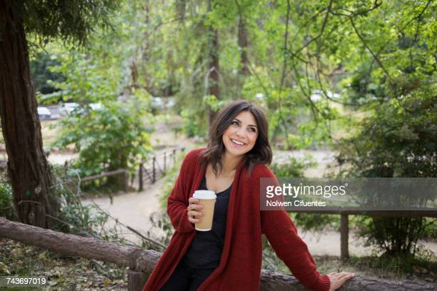 happy woman looking away while holding disposable glass in park - mid adult woman sweater stock pictures, royalty-free photos & images