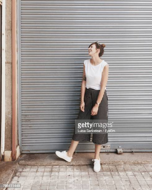 Happy Woman Looking Away While Standing Against Closed Shutter
