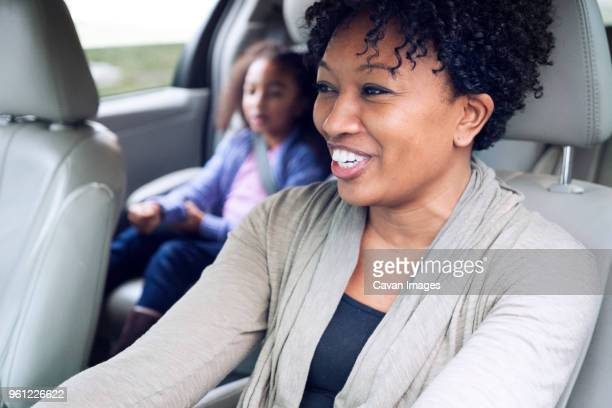 happy woman looking away while traveling with daughter in car - family inside car stock photos and pictures