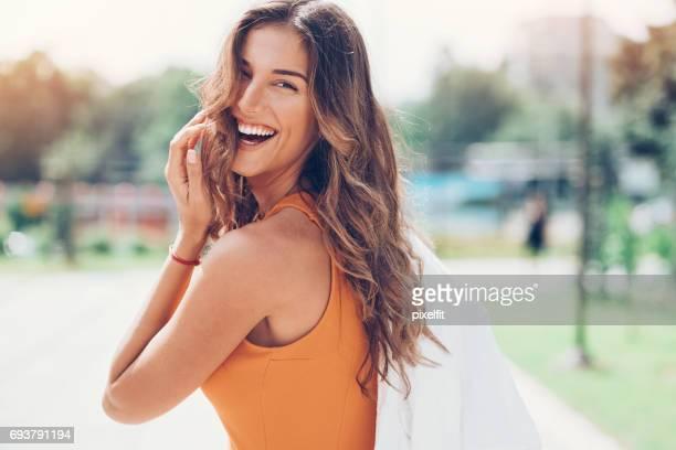 Mujer feliz mirando hacia atrás sobre el hombro