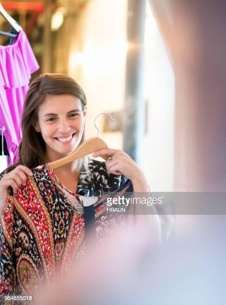 gelukkige vrouw in spiegel kijken terwijl het proberen jurk - the past stockfoto's en -beelden
