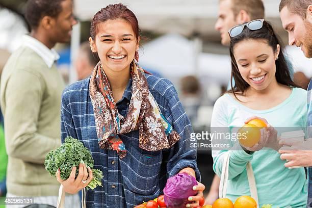 Mulher feliz olhando para que produtos hortícolas no mercado local agricultores
