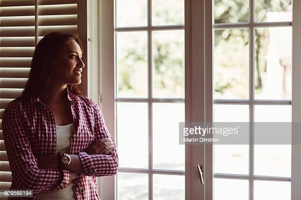 Happy woman looking through the window