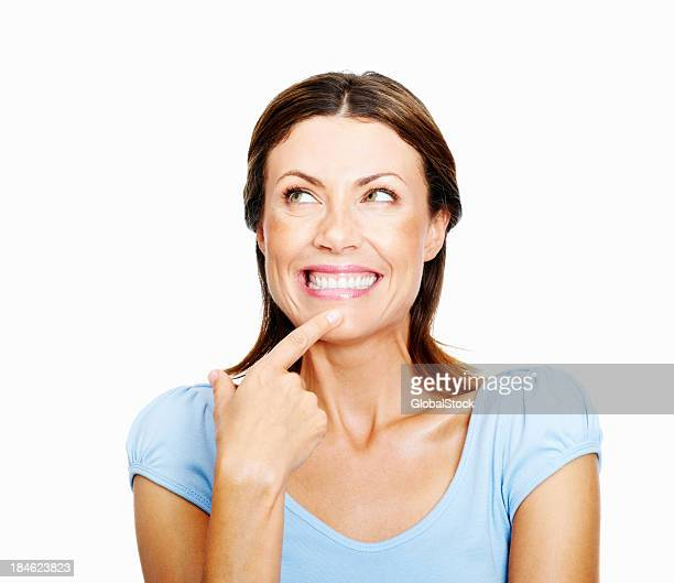Happy woman looking up with her finger on her chin