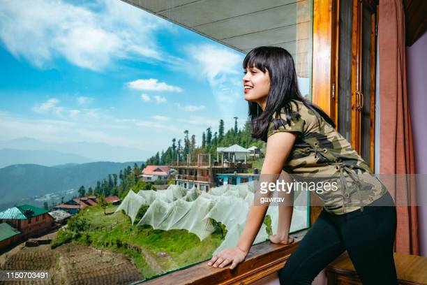 happy woman looks at scenic view through holiday villa's window. - shimla stock pictures, royalty-free photos & images