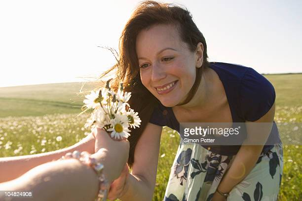 Happy woman looks at wild flowers