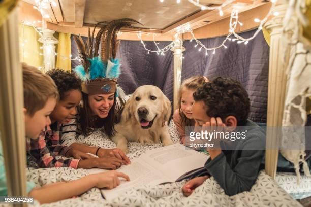 Mujer feliz en una tienda de campaña con grupo de chicos y un perro y leyendo un libro.