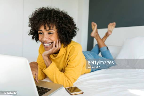 happy woman lying on bed using laptop - solo 2018 film stock pictures, royalty-free photos & images