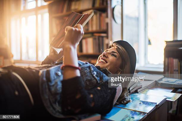 Happy woman lying on books while reading one of it.