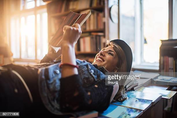 に横たわる幸せな女性の書籍を読みながらのます。