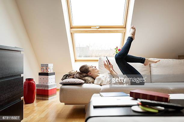 Happy woman lying on couch using cell phone