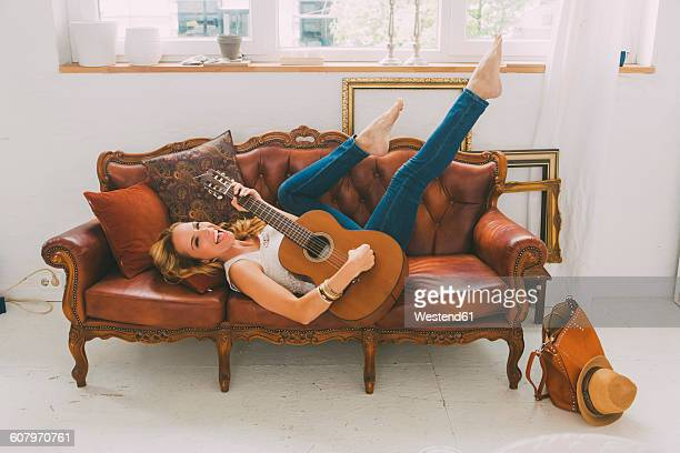 happy woman lying on leather couch playing guitar - blonde long legs stock pictures, royalty-free photos & images
