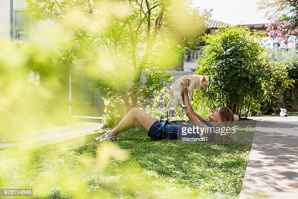 Happy woman lying on meadow in the garden with her Chihuahua