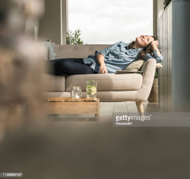 happy woman lying on the couch at home - sofa stock-fotos und bilder