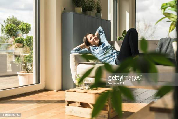 happy woman lying on the couch at home - hands behind head stock pictures, royalty-free photos & images