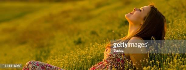glückliche frau liegt auf der sommerwiese - verführerische frau stock-fotos und bilder