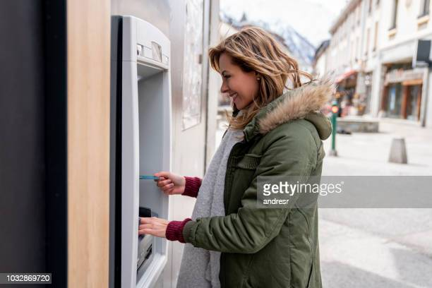 happy woman making a cash withdrawal at an atm - atm stock pictures, royalty-free photos & images