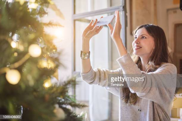 happy woman making a photo of her christmas tree. - social media marketing stock pictures, royalty-free photos & images