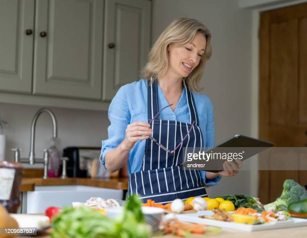 happy woman making dinner at home following an online tutorial - following stock pictures, royalty-free photos & images