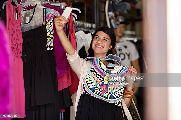 Happy woman making selfie while trying dress
