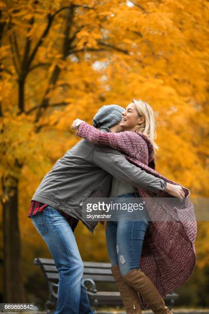 Happy woman meeting with her boyfriend in autumn park.