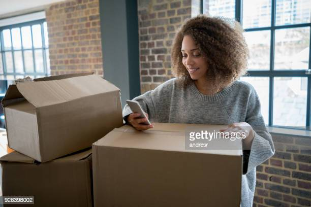 happy woman moving house - unpacking stock pictures, royalty-free photos & images