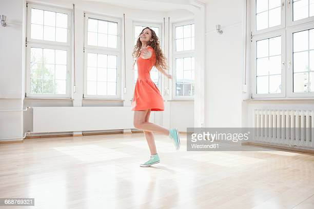 Happy woman moving in empty apartment