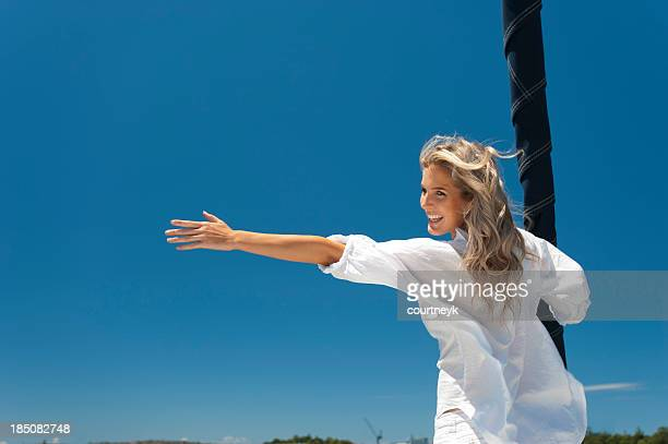 Happy woman on a sailboat with clear blue sky