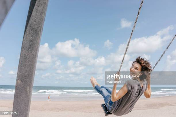 happy woman on a swing on the beach - swing stock pictures, royalty-free photos & images