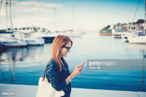 happy woman on a vacation texting at the marina - stereotypically upper class stock pictures, royalty-free photos & images