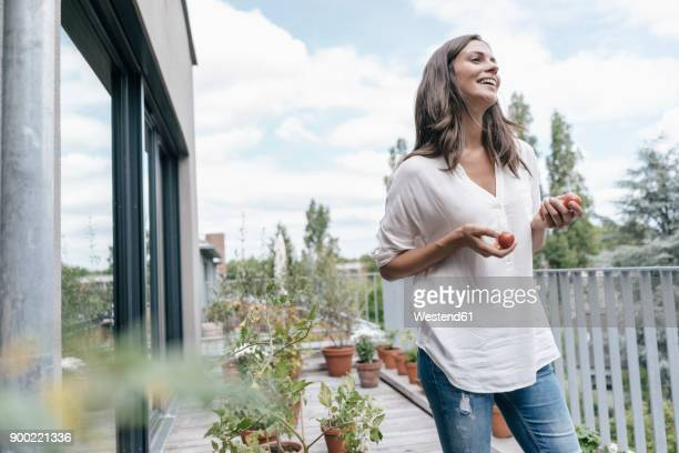 Happy woman on balcony holding tomatoes