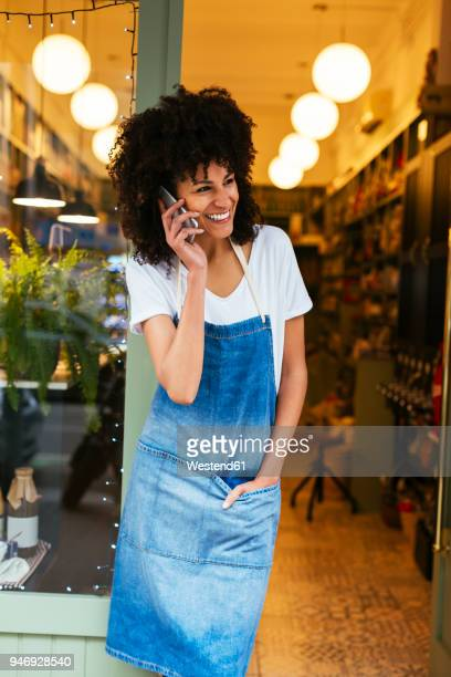 Happy woman on cell phone standing in entrance door of a store