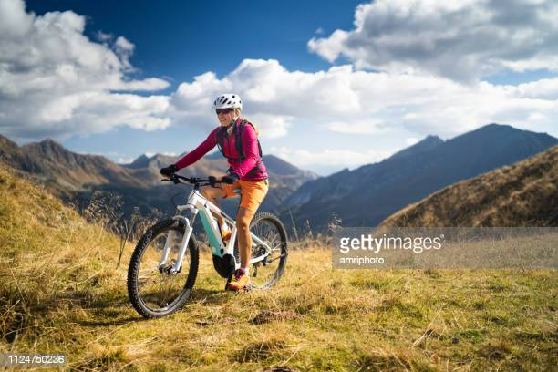 happy woman on electric mountain bike high up in european mountains - hybrid vehicle stock pictures, royalty-free photos & images