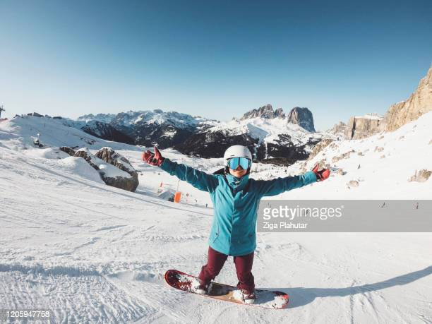 happy woman on snow board holding her hands up in the air - ski holiday stock pictures, royalty-free photos & images