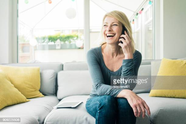 happy woman on the phone on couch - am telefon stock-fotos und bilder